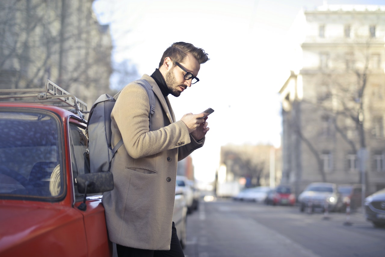 man using phone in the road