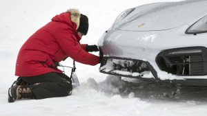 man checking his car in the snow